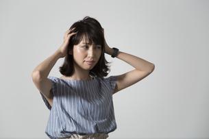 頭を抱える若い女性の写真素材 [FYI01190911]