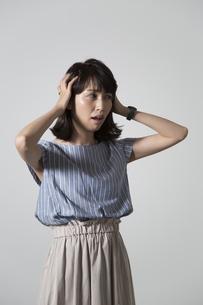 頭を抱える若い女性の写真素材 [FYI01190912]