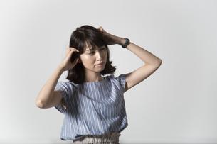 頭を抱える若い女性の写真素材 [FYI01190914]