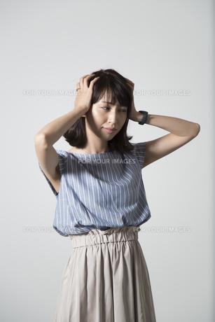頭を抱える若い女性の写真素材 [FYI01190915]