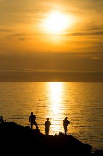夕暮れの海辺と磯釣りの写真素材 [FYI01190929]