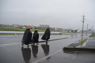 ドシャ降りの中を行く托鉢修行僧の写真素材 [FYI01191924]