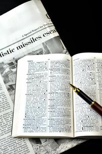 英字新聞と辞書とペンの写真素材 [FYI01192549]