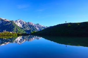 朝日を浴びた新緑の八方池と白馬三山と登山者の写真素材 [FYI01194605]