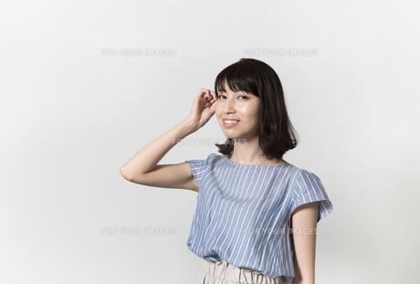 髪をかきあげる若い女性の写真素材 [FYI01195482]