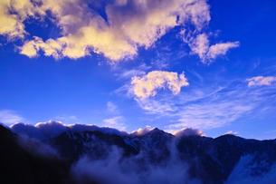夕陽を浴びて輝く雲と白馬三山の写真素材 [FYI01195635]