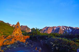 八方尾根から見た朝日を浴びた北アルプスと息ケルン(第三ケルン)の写真素材 [FYI01195643]