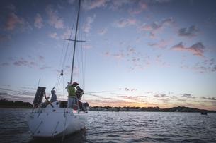 夕暮れのヨットと釣りをする人々の写真素材 [FYI01196024]