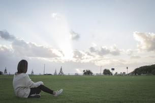 空を見る芝生の上に座る女性の写真素材 [FYI01196029]