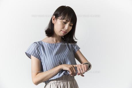 時計を見る若い女性の写真素材 [FYI01196328]