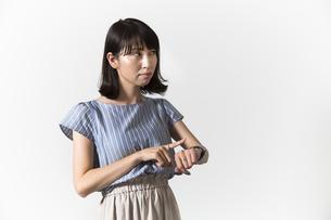 時計を見る若い女性の写真素材 [FYI01196329]