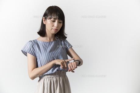 時計を見る若い女性の写真素材 [FYI01196330]
