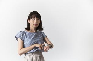 時計を見る若い女性の写真素材 [FYI01196331]