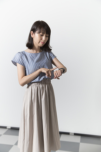 時計を見る若い女性の写真素材 [FYI01196333]