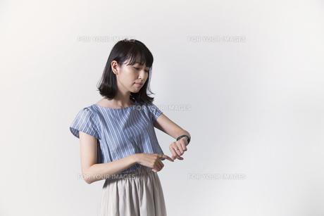 時計を見る若い女性の写真素材 [FYI01196335]