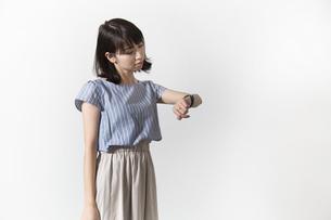 時計を見る若い女性の写真素材 [FYI01196336]