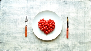 白皿にハート型に盛り付けたチェリートマトの写真素材 [FYI01198969]