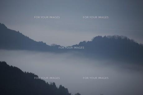 濃霧に覆われた町並みと山々の写真素材 [FYI01199139]
