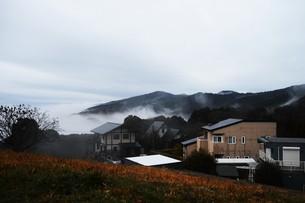 濃霧に覆われた町並みと山々の写真素材 [FYI01199144]