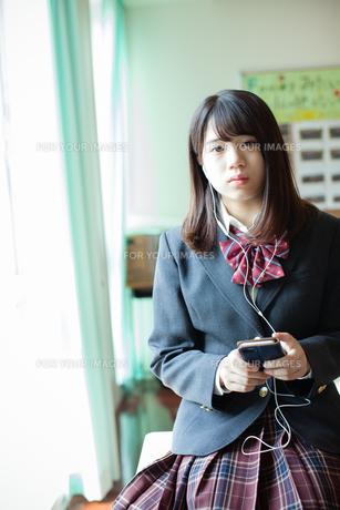 スマートフォンで音楽を聞く女性生徒の写真素材 [FYI01199213]