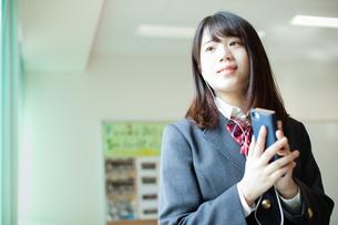 スマートフォンで音楽を聞く女性生徒の写真素材 [FYI01199215]