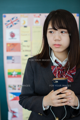スマートフォンで音楽を聞く女性生徒の写真素材 [FYI01199217]
