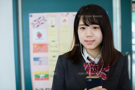 スマートフォンで音楽を聞く女性生徒の写真素材 [FYI01199218]