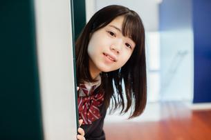 扉から顔を出す女性生徒の写真素材 [FYI01199221]