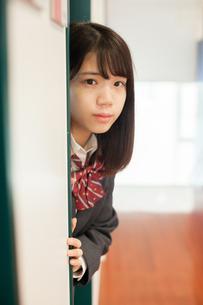 扉から顔を出す女性生徒の写真素材 [FYI01199223]