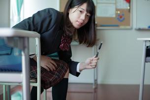 教室でペンを拾う女子生徒の写真素材 [FYI01199225]