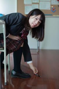 教室でペンを拾う女子生徒の写真素材 [FYI01199226]