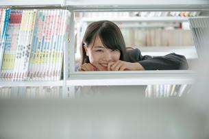 本棚の向こう側にいる女子生徒の写真素材 [FYI01199257]