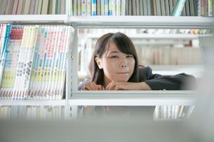 本棚の向こう側にいる女子生徒の写真素材 [FYI01199258]