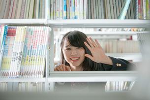 本棚の向こう側にいる女子生徒の写真素材 [FYI01199259]