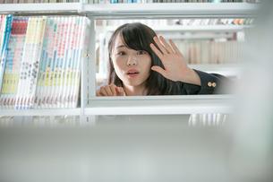 本棚の向こう側にいる女子生徒の写真素材 [FYI01199260]