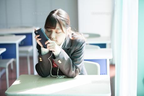 放課後の教室で音楽を聞く女子高生の写真素材 [FYI01199281]