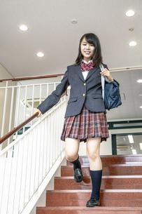 スクールバックを肩に掛け学校の階段を降りる制服姿の女子高生の写真素材 [FYI01199360]