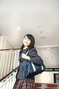 スクールバックを肩に掛け学校の階段を笑顔で降りる制服姿の女子高生の写真素材 [FYI01199361]