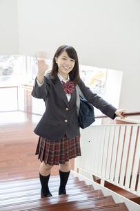 スクールバックを肩に掛け学校の階段で笑顔で手を振る制服姿の女子高生の写真素材 [FYI01199362]