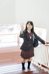 スクールバックを肩に掛け学校の階段で笑顔で手を振る制服姿の女子高生の写真素材 [FYI01199363]