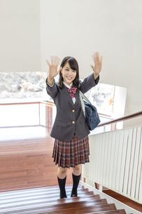 スクールバックを肩に掛け学校の階段で笑顔で両手を振る制服姿の女子高生の写真素材 [FYI01199365]