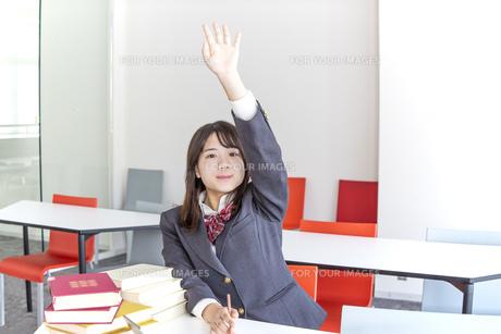 制服姿で手を上げ応える女子高生の写真素材 [FYI01199370]