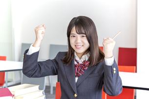 学校の木洋室でガッツポーズをする女子高生の写真素材 [FYI01199372]
