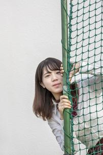 球技用ネットから顔を出す女子高生の写真素材 [FYI01199377]