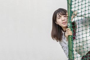 球技用ネットから顔を出す女子高生の写真素材 [FYI01199378]