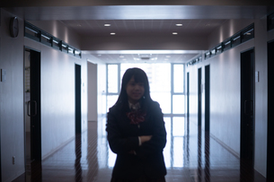 廊下で笑みを浮かべ腕組みする女子高生の写真素材 [FYI01199387]