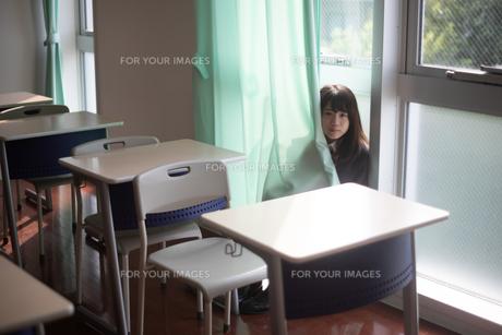 学校の教室のカーテンに隠れる女子高生の写真素材 [FYI01199388]