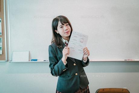 テストの答案を持つ女子高生の写真素材 [FYI01199603]