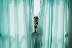 カーテンから顔を出す女子高生3の写真素材 [FYI01199604]