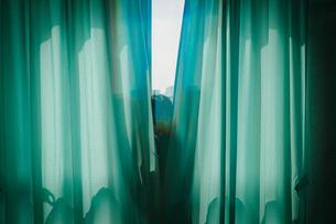 カーテンから顔を出す女子高生2の写真素材 [FYI01199605]